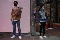 A man wearing protective face mask waits at a street corner with a bouquet on Valentine's Day in Hong Kong, Friday, Feb. 14, 2020. China on Friday reported another sharp rise in the number of people infected with a new virus, as the death toll neared 1,400. (AP Photo/Kin Cheung)