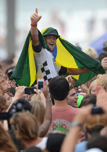 Alejo Muniz, of Brazil, is carried on the shoulders of fans after his win in the men's finals of the Vans US Open of Surfing competition in Huntington Beach, Calif., on Sunday, July 28, 2013. (AP Photo/The Orange County Register, Christine Cotter) MAGS OUT; LOS ANGELES TIMES OUT.