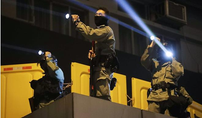 Officers point flashlights at anti-government protesters at Mong Kok Police Station on December 31. Photo: Edmond So