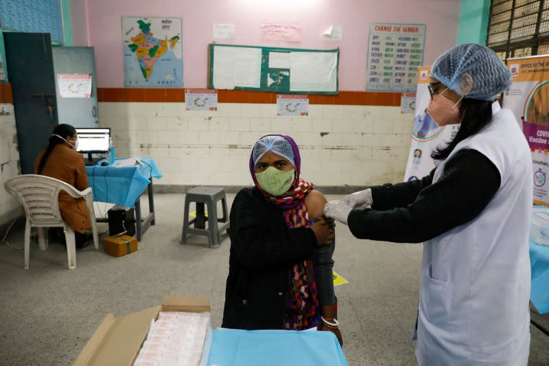 FILE PHOTO: A health worker and a volunteer take part in a nationwide trial run of coronavirus disease (COVID-19) vaccine delivery systems, inside a school, which has been converted into a temporary vaccination centre, in New Delhi