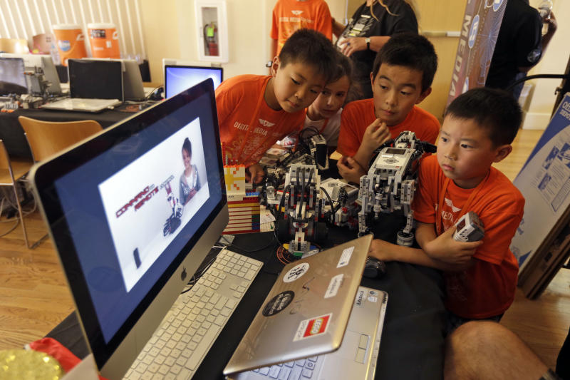 In this Aug. 14, 2013, photo, children look at a computer presentation on how to assemble Lego parts during a Digital Media Academy workshop in Stanford, Calif. Lego's new Mindstorms sets rolling out next month are keenly anticipated by Silicon Valley engineers_many of whom were drawn to the tech sector by the flagship kits that came on the market in 1998, introducing computerized movement to the traditional snap-together toy blocks and allowing the young innovators to build their first robots. (AP Photo/Marcio Jose Sanchez)