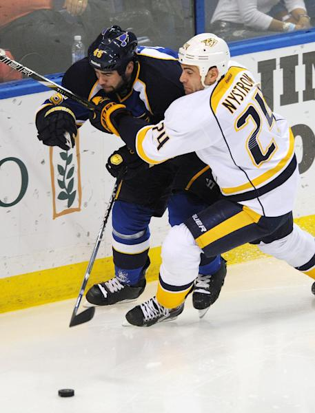 Nashville Predators' Eric Nystrom (24) and St. Louis Blues' Roman Polak (46), of Czech Republic, battle for the puck during the second period of an NHL hockey game Thursday, Oct. 3, 2013, in St. Louis. (AP Photo/Bill Boyce)
