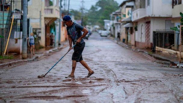 PHOTO: A man sweeps mud from a street after Tropical Storm Isaias swept through the area in Mayaguez, Puerto Rico, July 30, 2020. (Ricardo Arduengo/AFP via Getty Images)