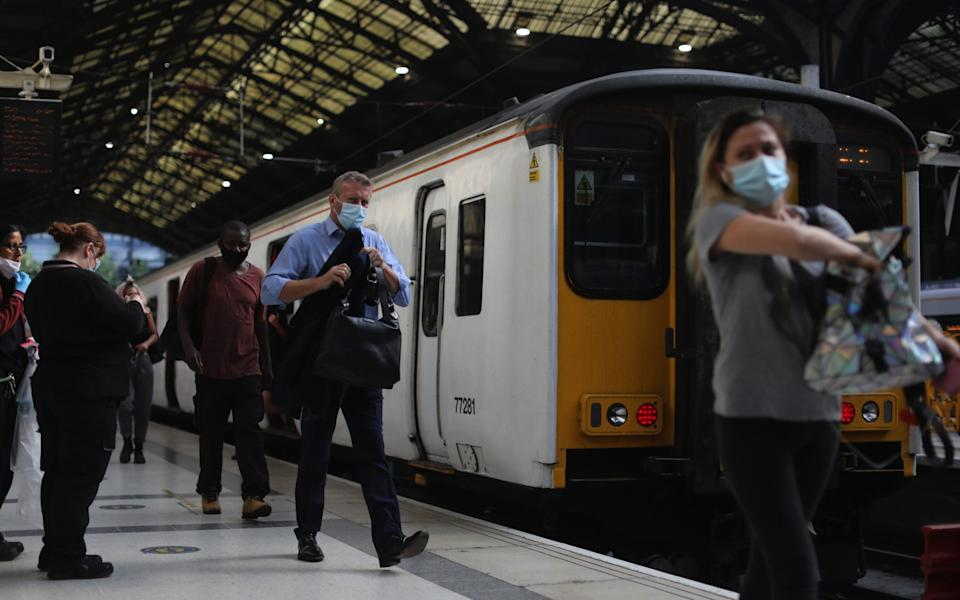 Commuters wearing protective face masks alight from a train at Liverpool Street railway station, during morning rush hour in London, U.K., on Wednesday, Aug. 12, 2020. The pandemic hit the U.K.hardestin Europe with the country's economy contracting more than 20% in the second quarter. Photographer: Simon Dawson/Bloomberg - Simon Dawson/Bloomberg
