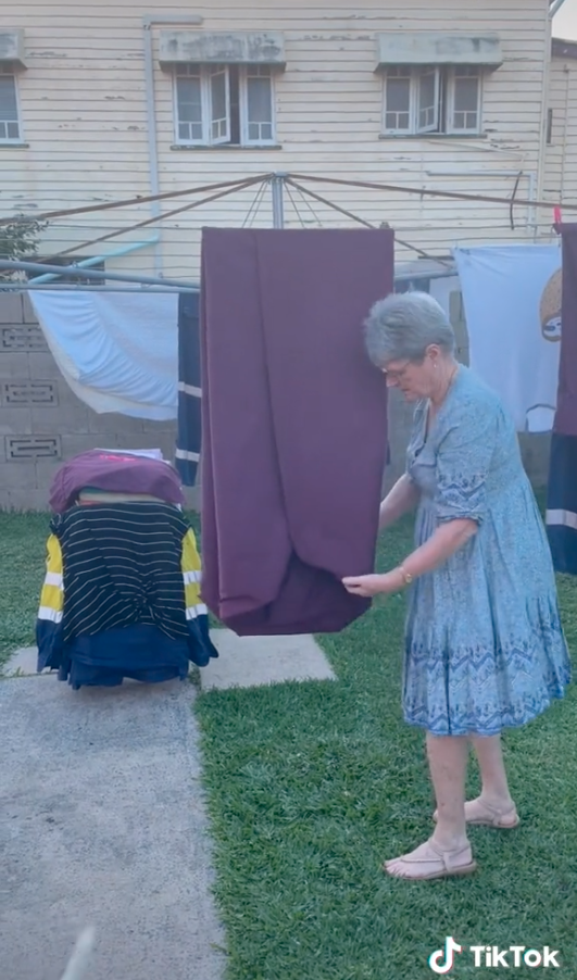 Woman folding a fitted sheet on a clothes line