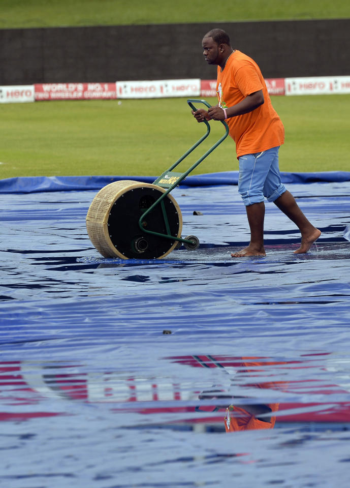 A groundsman works to remove water from the field after  rain during the sixth match of the Tri-Nation series between India and Sri Lanka at the Queen's Park Oval stadium in Port of Spain on July 9, 2013. The match is at halt due to rain. AFP PHOTO/Jewel Samad