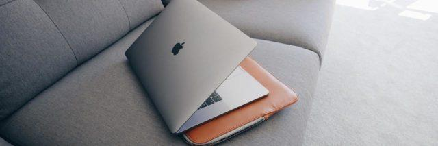 Mac laptop sitting on top of a leather computer case on a gray couch