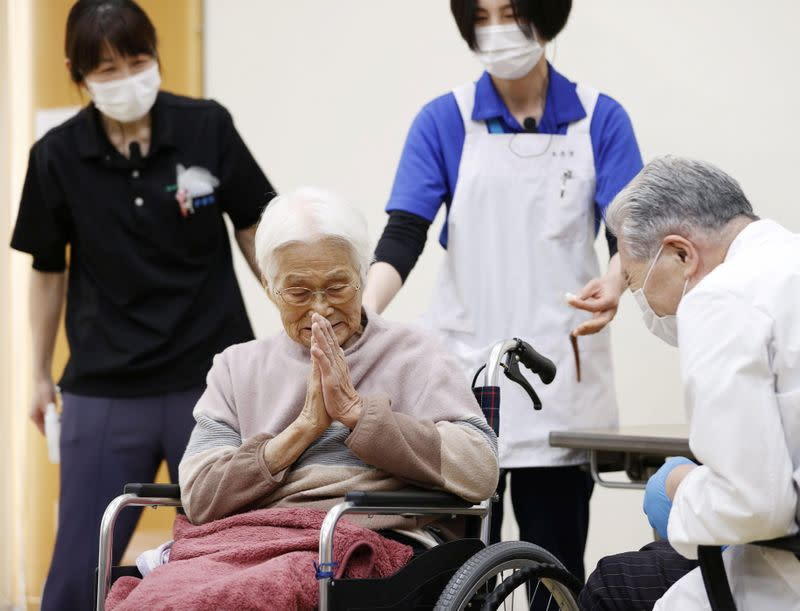 An elderly woman gestures to express gratitude after receiving a coronavirus disease (COVID-19) vaccination in Itami, western Japan