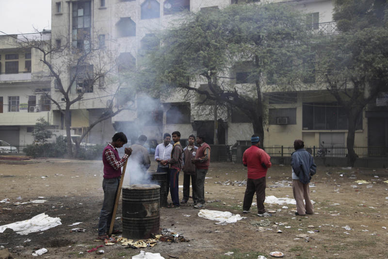 Indians burn the leftover food after a wedding in New Delhi, India, Wednesday, Feb. 5, 2014. New Delhi's worsening air pollution has drawn comparisons with Beijing, the world's pollution poster child. (AP Photo/Tsering Topgyal)