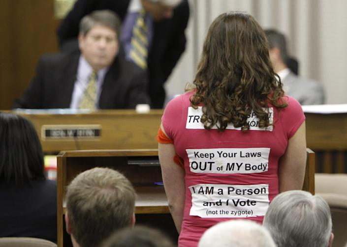 A woman wearing stickers supporting Women's rights speaks during a meeting of the Senate Education and Health committee at the Capitol in Richmond, Va., Thursday, Feb. 23, 2012. (AP Photo/Steve Helber)