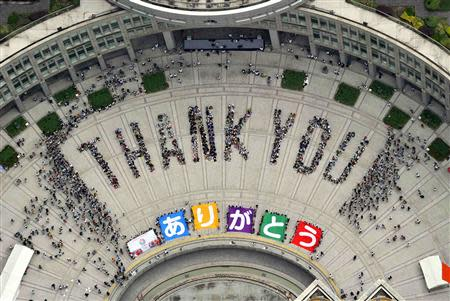 """An aerial view shows people sitting in formation to the words """"thank you"""" and displaying signs that collectively read """"Arigato"""" during an event celebrating Tokyo being chosen to host the 2020 Olympic Games, in Tokyo"""