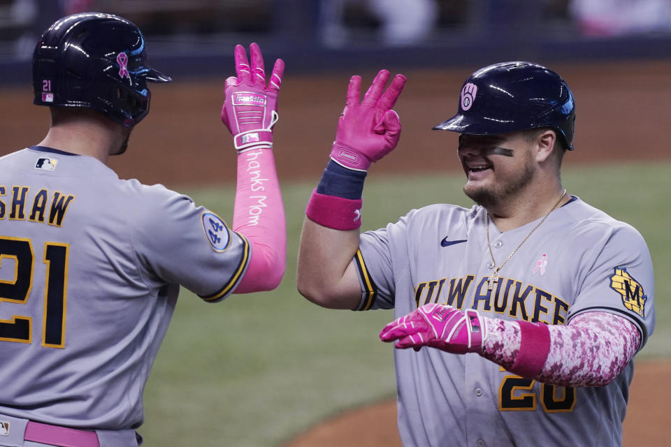 Milwaukee Brewers' Daniel Vogelbach (20) signals to Travis Shaw (21) after hitting a solo home run in the fourth inning of a baseball game against the Miami Marlins, Sunday, May 9, 2021, in Miami. (AP Photo/Marta Lavandier)
