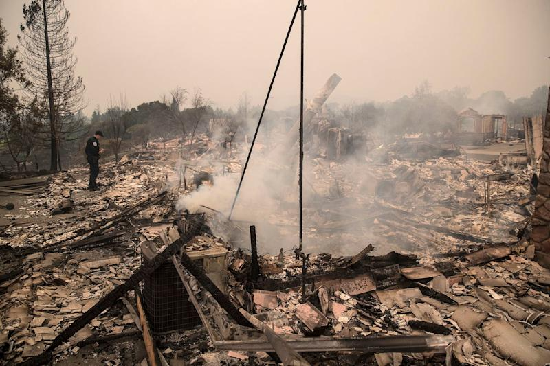 A police officer looks over the destruction of a home in Santa Rosa.