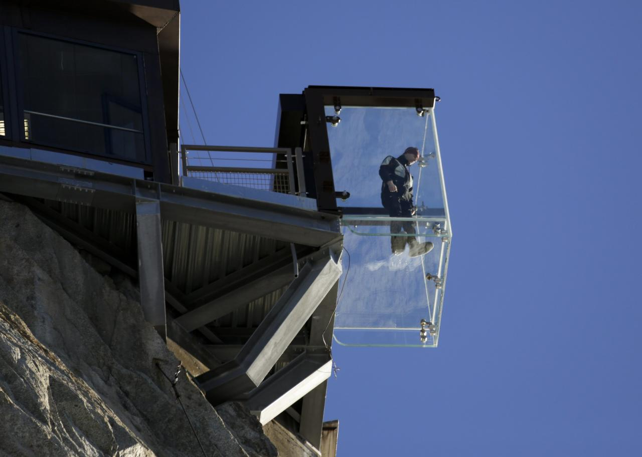 A man, wearing slippers to protect the glass floor, stands in the 'Step into the Void' installation during a press visit at the Aiguille du Midi mountain peak above Chamonix, in the French Alps, December 17, 2013. The Chamonix Skywalk is a five-sided glass structure installed on the top terrace of the Aiguille du Midi (3842m), with a 1,000 metre drop below, where visitors can step out from the terrace, giving the visitors the impression of standing in the void. The glass room will open to the public on December 21, 2013. REUTERS/Robert Pratta (FRANCE - Tags: SOCIETY TRAVEL CITYSCAPE)