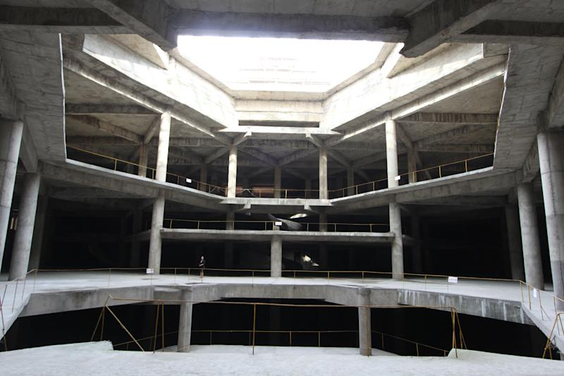 In this Sept. 23, 2012 photo released by Koryo Group on Wednesday, Sept. 26, 2012, a visitor, center left, stands on the ground floor of the 105-story Ryugyong Hotel in Pyongyang, North Korea. After years of standing unfinished, construction on the exterior of the massive hotel resumed three years ago but the hotel has not yet opened to the public. This photo taken by the Beijing-based Koryo Tours shows that the interior remains unfinished. (AP Photo/Koryo Group) NO SALES, EDITORIAL USE ONLY