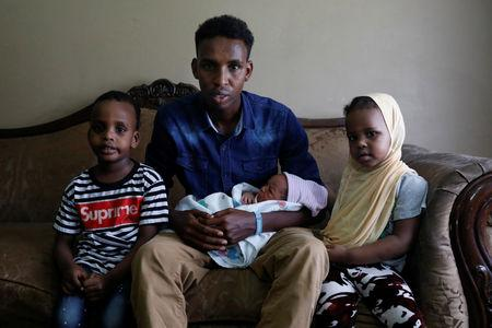 Aden Hussein Hassan with his daughter Asmo, 2 days, son Mohammed, 4, and daughter Adno, pose for a picture inside their apartment in Columbus, Ohio, U.S., August 8, 2018.     REUTERS/Shannon Stapleton