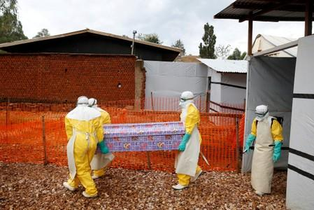 FILE PHOTO: Health workers dressed in Ebola protective suits carry a coffin with the body of Congolese woman Kahambu Tulirwaho, who died of Ebola, as it is transported for a burial from the Ebola treatment centre in Butembo