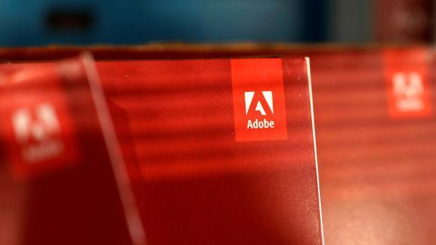 Three red boxes of Adobe software with their logos facing forward are lit by the light from a window.