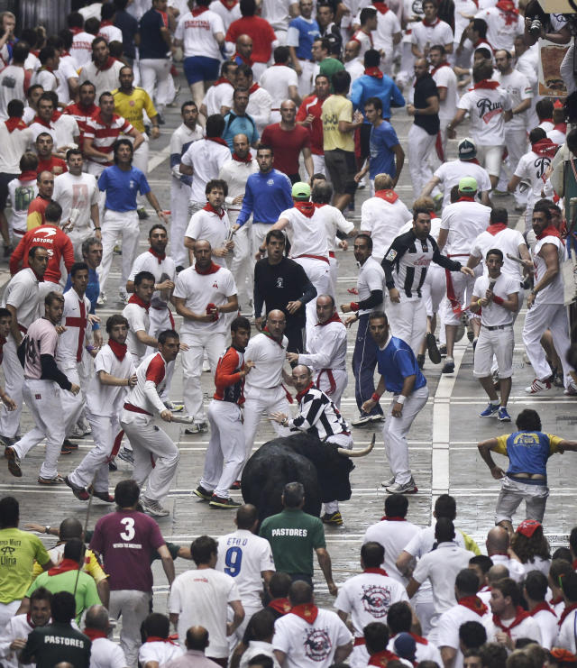 """Runners prepare to dash away in front of an """"El Pilar"""" fighting bull during the running of the bulls at the San Fermin festival, in Pamplona, Spain, Friday, July 12, 2013. Revelers from around the world arrive to Pamplona every year to take part in some of the eight days of the running of the bulls. (AP Photo/Alvaro Barrientos)"""