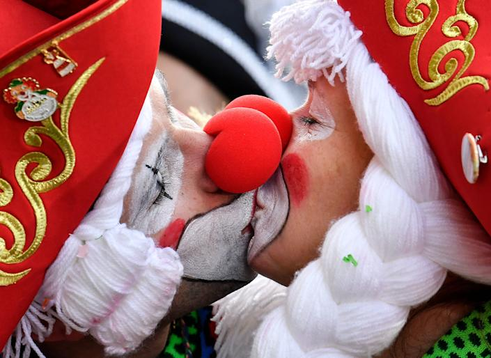 Two revellers kiss for photographers in Cologne's city center when thousands of revelers dressed in carnival costumes celebrate the start of the street carnival in Cologne, Germany, Thursday, February 28, 2019.