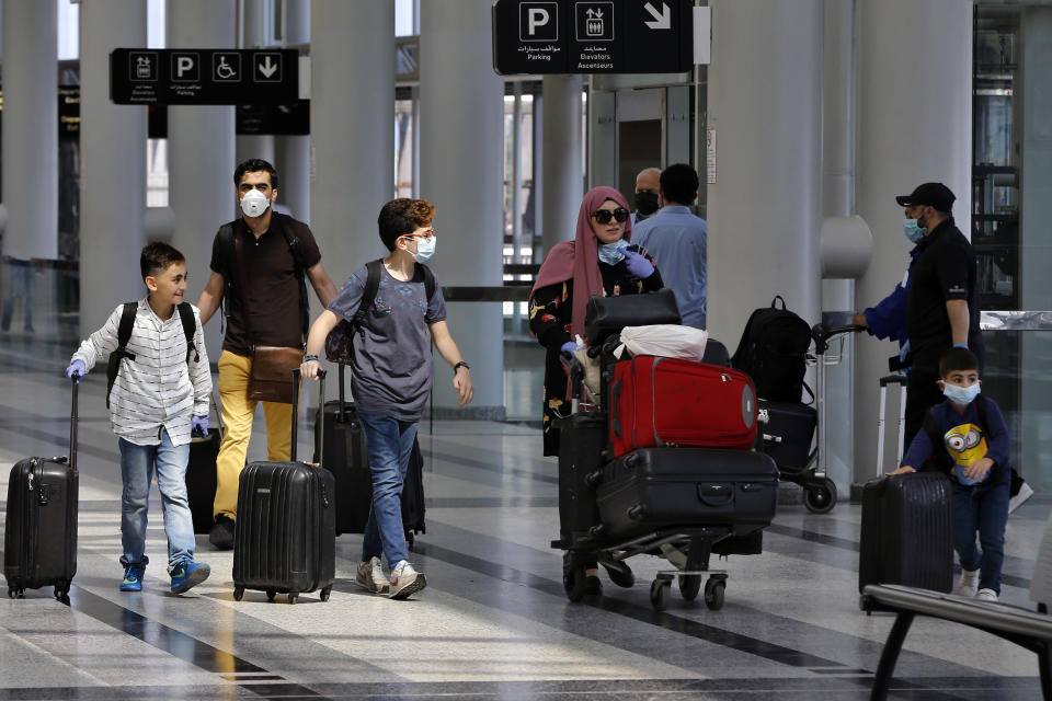 Travelers push their luggage at the departure terminal of the Rafik Hariri International Airport in Beirut, Lebanon, Wednesday, July 1, 2020. Beirut's airport is partially reopening after a three-month shutdown and Lebanon's cash-strapped government is hoping that Thousands of Lebanese expatriates will return for the summer, injecting dollars into the country's sinking economy. (AP Photo/Bilal Hussein)