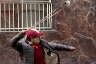 A supporter of former President Evo Morales throws a stone to police, in La Paz, Bolivia, Friday, Nov. 15, 2019. Bolivia's new interim president Jeanine Anez faces the challenge of stabilizing the nation and organizing national elections within three months at a time of political disputes that pushed Morales to fly off to self-exile in Mexico after 14 years in power. (AP Photo/Natacha Pisarenko)
