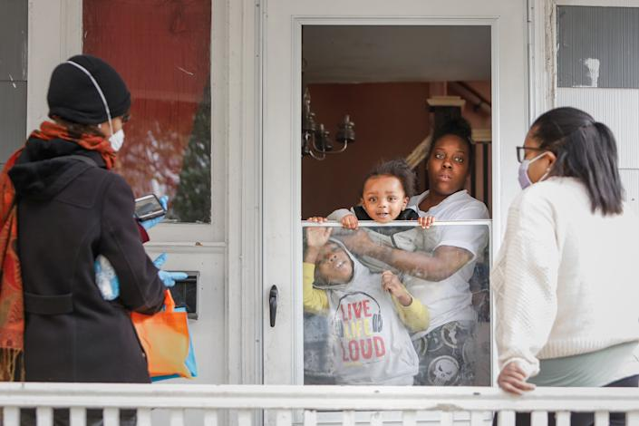 Sister Jenthia and Dr. Angela Branche hand out coronavirus disease (COVID-19) survival kit to Natalie Hall as part of a door-to-door outreach program to the Black community to increase vaccine trial participation in Rochester, New York, U.S., October 17, 2020. Picture taken October 17, 2020.  REUTERS/Lindsay DeDario