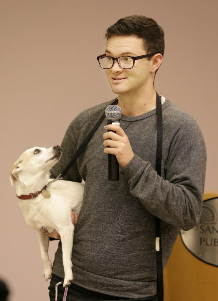 Sex worker Cyd Nora holds his dog Farrah as he speaks at a meeting with others who claim that the California Victims Compensation Board discriminates against sex workers by denying them benefits after having been raped in San Francisco, Tuesday, Nov. 12, 2013. (AP Photo/Jeff Chiu)