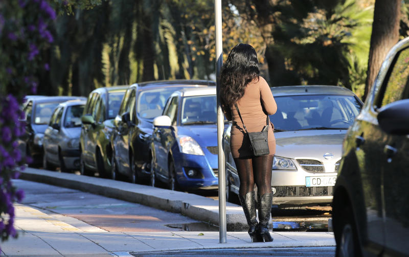 "A prostitute waits for a client in a street of Nice southern France, Thursday, Nov 21, 2013.France's government is pushing one of Europe's toughest laws against prostitution and sex trafficking, and other countries are watching closely. Advocates hope that a draft French law going to parliament Wednesday will help change long-held attitudes toward the world's oldest profession _ by punishing the customer and protecting the prostitute. But the bill is facing resistance in a country with a libertine reputation and a Mediterranean macho streak, and has prompted petitions defending those who buy sex. Signatories include screen icon Catherine Deneuve _who played a prostitute in the cult film ""Belle de Jour"" _ and crooner Charles Aznavour.. (AP Photo)"