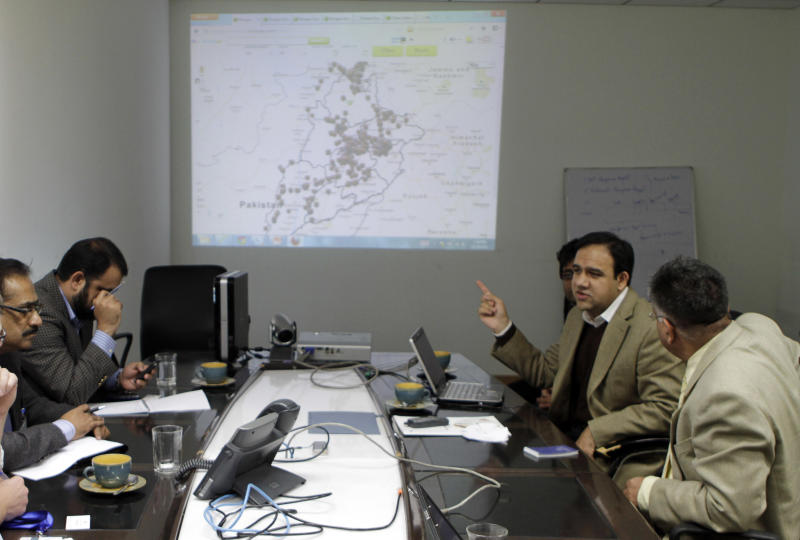 This Wednesday, Dec. 19, 2012 photo shows Umar Saif, second from right, as he briefs others about an anti-corruption program in Lahore, Pakistan. The program, which is being run by the Punjab Information Technology Board, uses a combination of telephone calls and text messages to get feedback from citizens conducting transactions with 12 different government departments, including those dealing with property, health, and emergency response. (AP Photo/K.M. Chaudary)