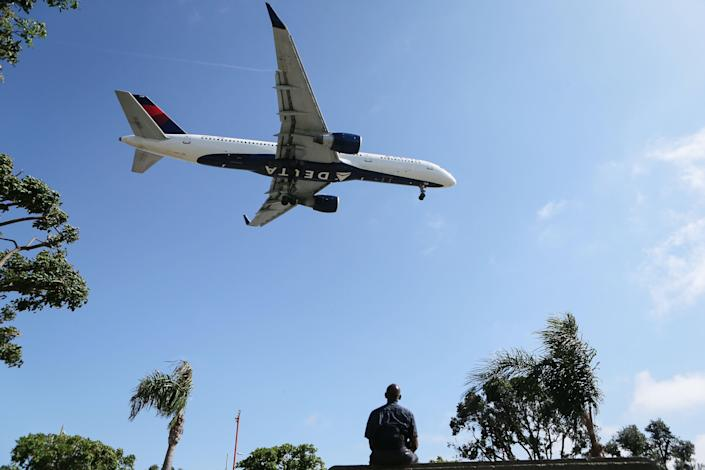 A man watches as a Delta Air Lines plane lands at Los Angeles International Airport on July 12, 2018 in Los Angeles, California. (Getty Images)