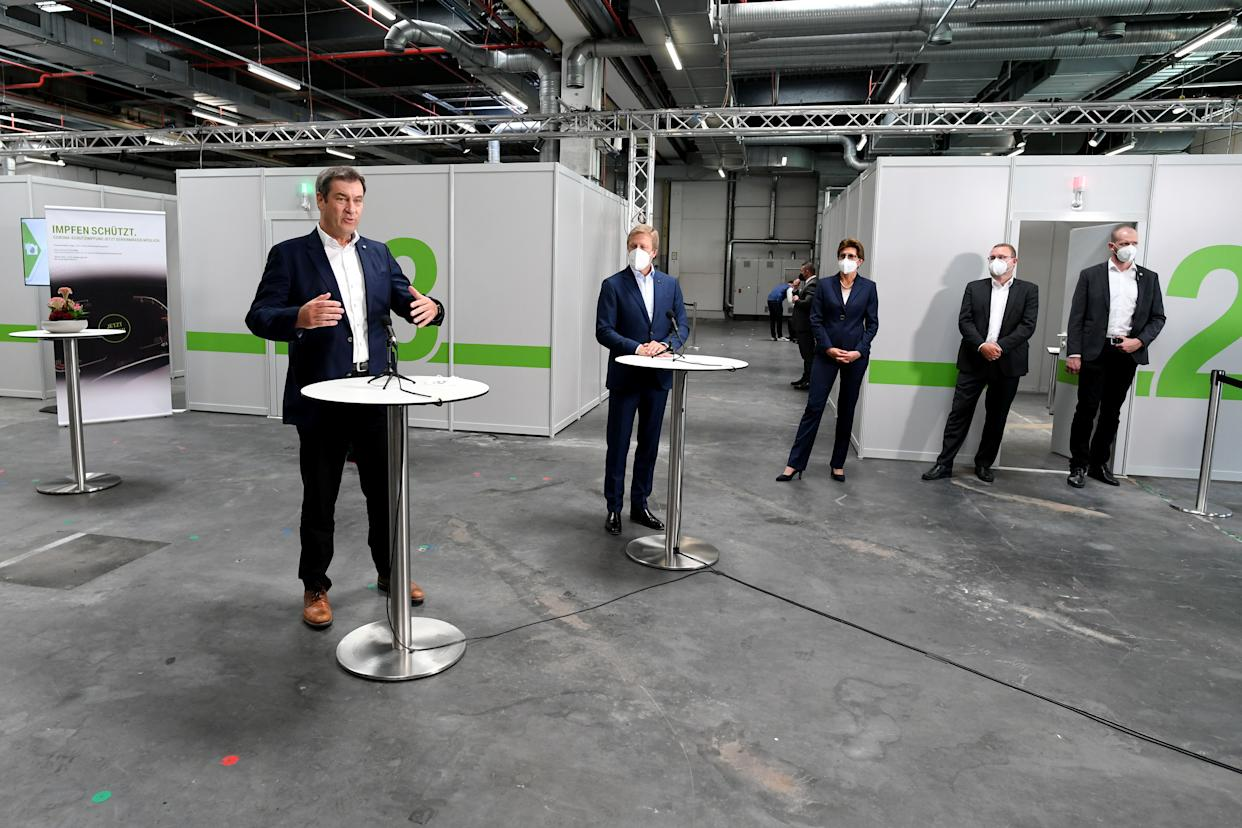 Bavarian State Premier Markus Soeder gestures next to BMW CEO Oliver Zipse as BMW starts to provide coronavirus disease (COVID-19) vaccinations for staff, in Munich, Germany, June 7, 2021. REUTERS/Andreas Gebert