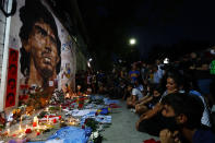 Soccer fans hold a vigil for Diego Maradona outside the stadium of Argentinos Juniors soccer club, where he started as a professional footballer, in Buenos Aires, Argentina, Wednesday, Nov. 25, 2020. The Argentine soccer great who was among the best players ever and who led his country to the 1986 World Cup title died from a heart attack at his home in Buenos Aires. He was 60. (AP Photo/Marcos Brindicci)