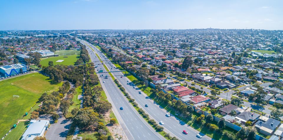 Cars driving on Monash freeway through Wheelers Hill suburb in Melbourne, Australia on sunny day - aerial panorama