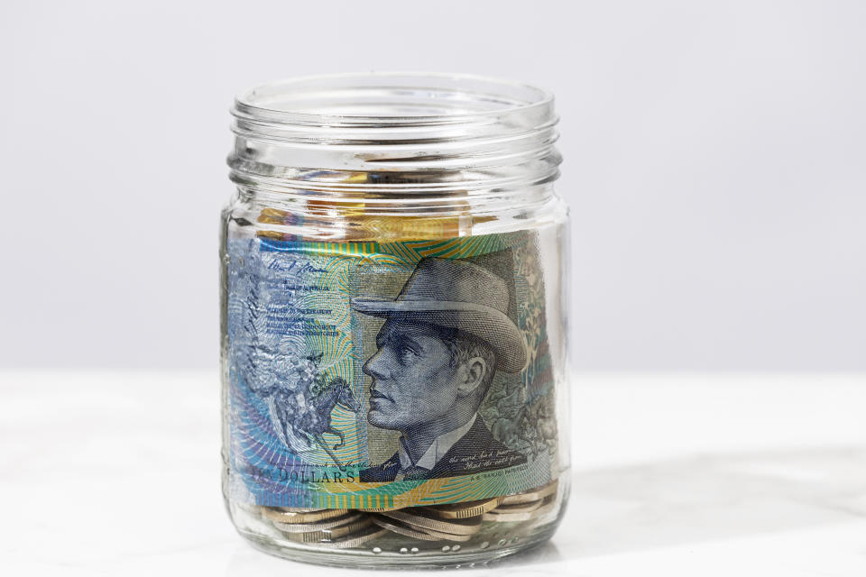 Australian ten dollar plastic currency note in a jar with coins.