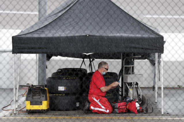 A crew member takes shelter under a tent as rain falls at the Darlington Raceway before the NASCAR Xfinity series auto race Tuesday, May 19, 2020, in Darlington, S.C. (AP Photo/Brynn Anderson)