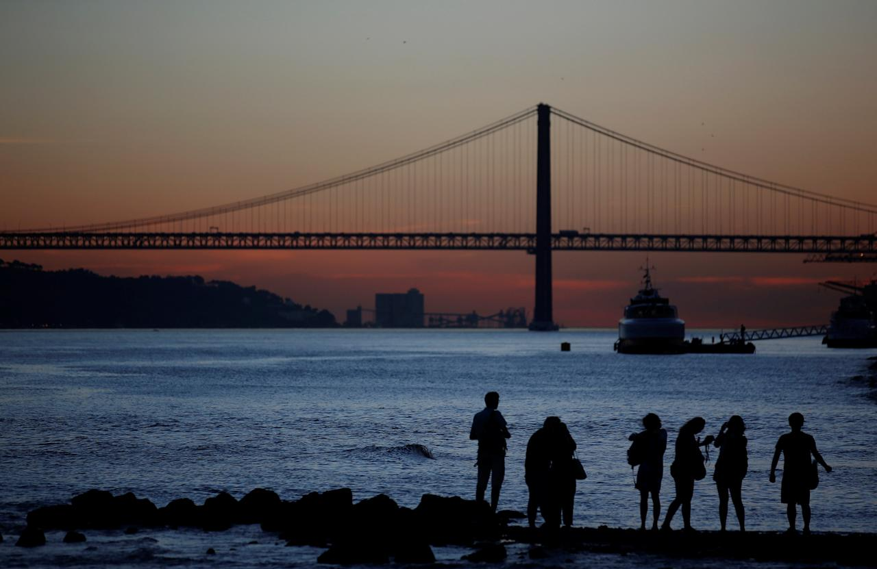 FILE PHOTO: Tourists looks the sunset at the Tagus river near the 25 April bridge in downtown Lisbon October 23, 2014.  REUTERS/Rafael Marchante/File Photo