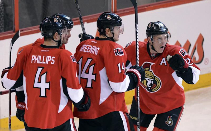 Ottawa Senators' Chris Neil, right, celebrates a first period goal against the Boston Bruins with teammates, from left, Chris Phillips, Zack Smith and Colin Greening during the first period of an NHL hockey game in Ottawa, Ontario on Friday, Nov. 15, 2013. (AP Photo/The Canadian Press, Sean Kilpatrick)