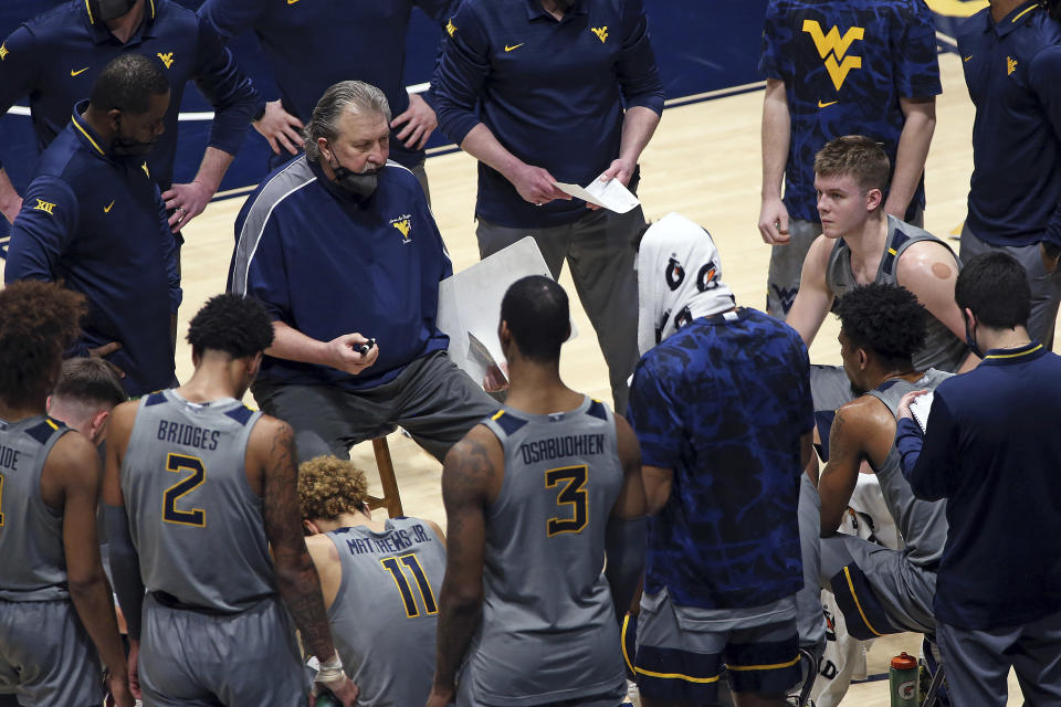 West Virginia coach Bob Huggins speaks with players during the second half of an NCAA college basketball game against Kansas State, Saturday, Feb. 27, 2021, in Morgantown, W.Va. (AP Photo/Kathleen Batten)