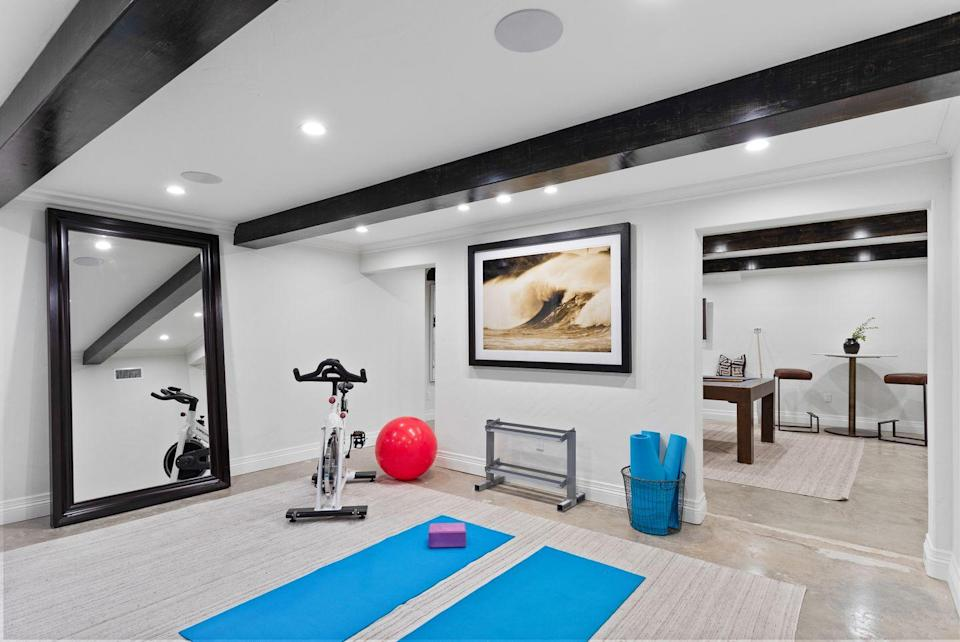 """<p>Take advantage of the cooler temps in the basement and install a home gym, yoga room, or whatever type of fitness center floats your boat. Use a mirror, like the one seen here in the basement of art director <a href=""""http://www.nourmand.com/real-estate/2501-n-vermont-ave-los-angeles-ca-90027/20-594522/95932126"""" rel=""""nofollow noopener"""" target=""""_blank"""" data-ylk=""""slk:L. Milton Wolf's L.A. home"""" class=""""link rapid-noclick-resp"""">L. Milton Wolf's L.A. home</a>, to make a space feel larger and to help you make sure your alignment is correct as you work out. </p>"""