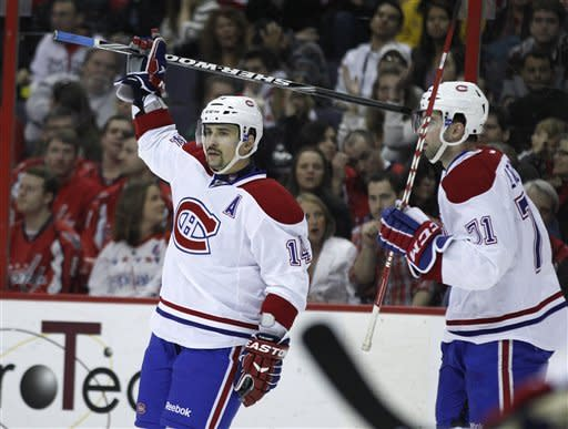 Montreal Canadiens center Tomas Plekanec (14) raises his stick after scoring a goal during the second period of an NHL hockey game against the Washington Capitals on Saturday, March 31, 2012 in Washington. At right is Montreal Canadiens center Louis Leblanc. (AP Photo/Evan Vucci)