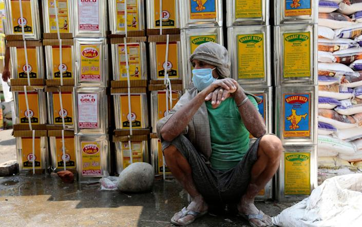 A laborer wearing a face mask rests at a warehouse in Jammu, India, Wednesday, July 29, 2020. (AP Photo/Channi Anand) - AP