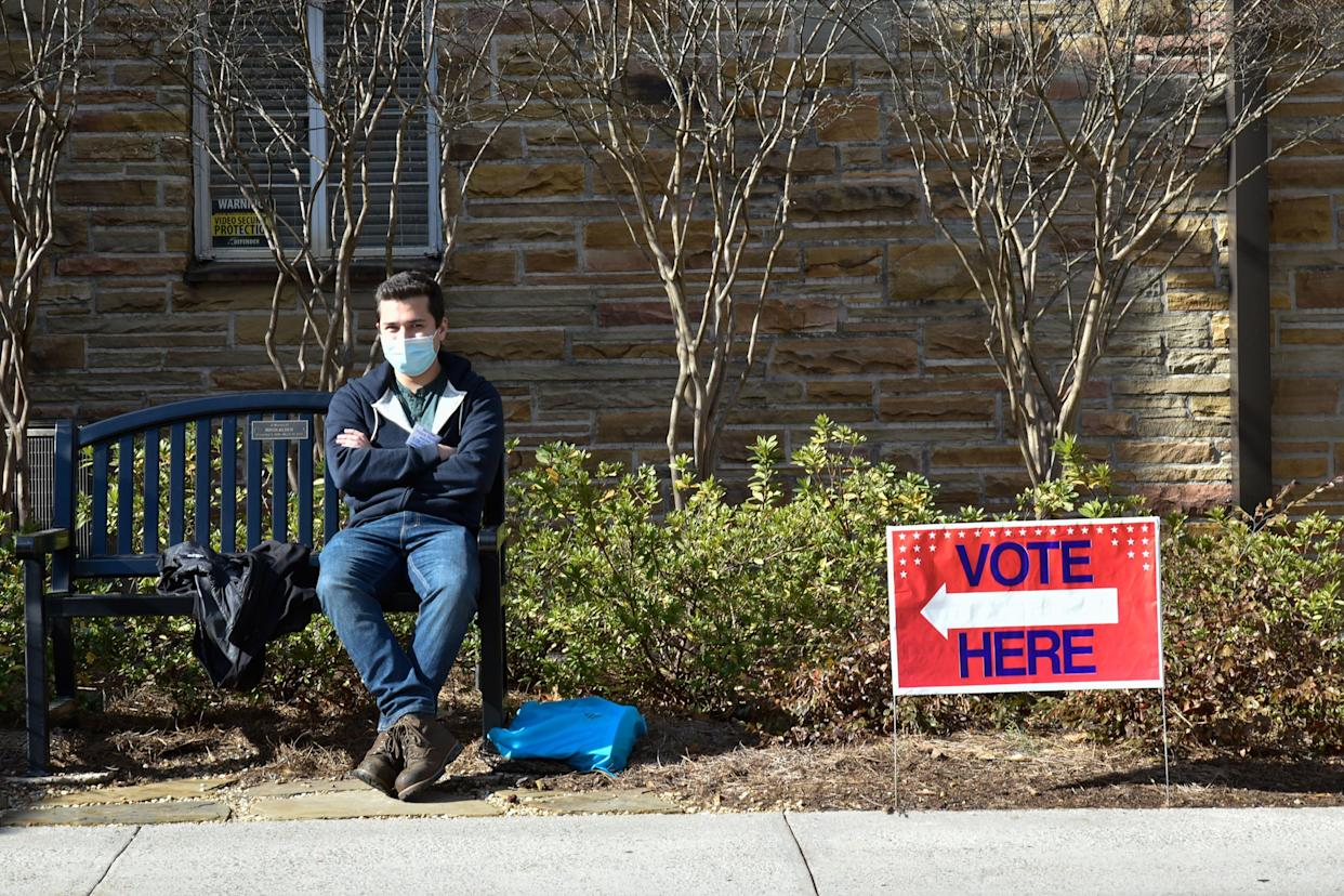 A man sits next to a vote sign