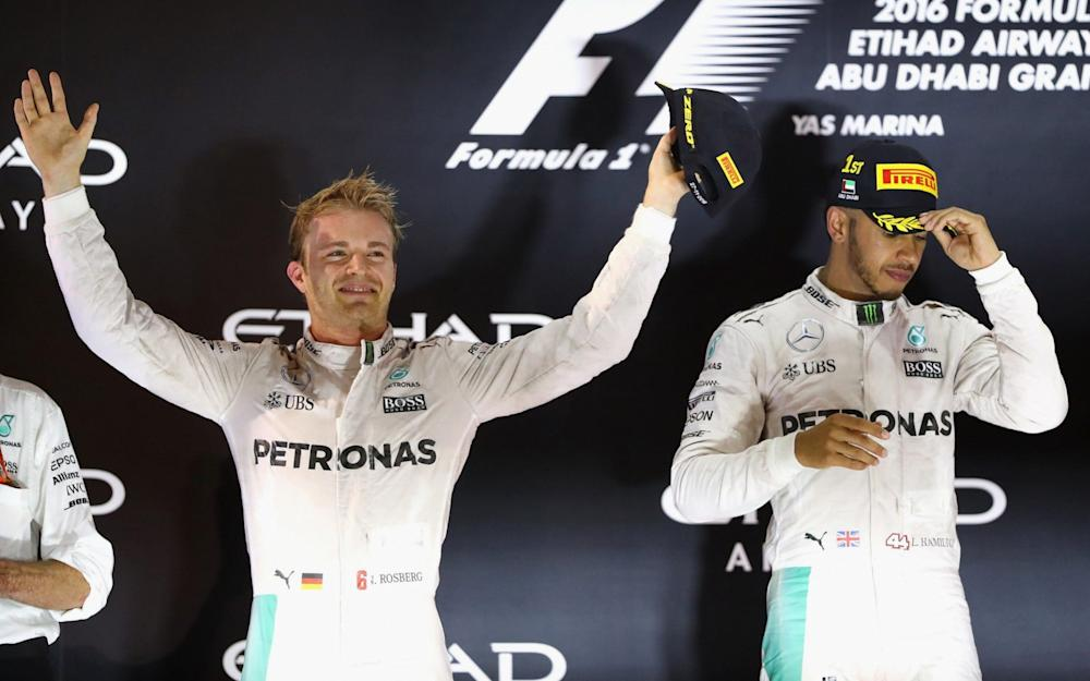 ABU DHABI, UNITED ARAB EMIRATES - NOVEMBER 27: Race winner Lewis Hamilton of Great Britain and Mercedes GP and second place finisher and World Drivers Champion Nico Rosberg of Germany and Mercedes GP on the podium during the Abu Dhabi Formula One Grand Prix at Yas Marina Circuit on November 27, 2016 in Abu Dhabi, United Arab Emirates. (Photo by Clive Mason/Getty Images) - Credit: Clive Mason/Getty