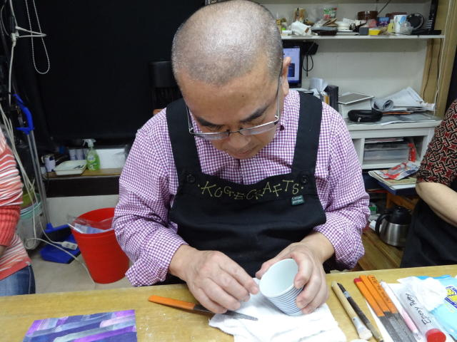 This Nov. 11, 2018 photo taken in Tokyo shows co-instructor Yoshiichiro Kuge checking whether the filler material is filed down enough to proceed to the next step at the Kuge Crafts workshop in Tokyo. Kintsugi is an ancient Japanese method of repairing broken pottery with gold that creates a new work of art. (Linda Lombardi via AP)