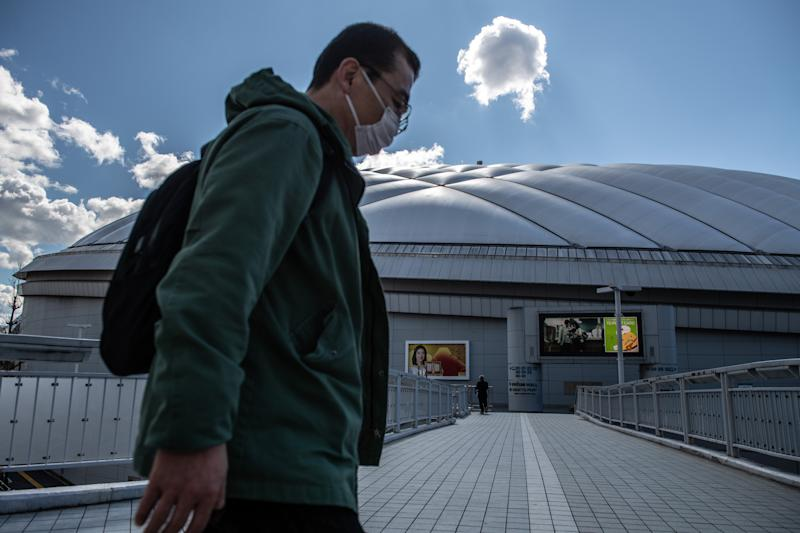 A man walks past Tokyo Dome where a number of events including pop concerts have been cancelled because of concerns over the Covid-19 virus.