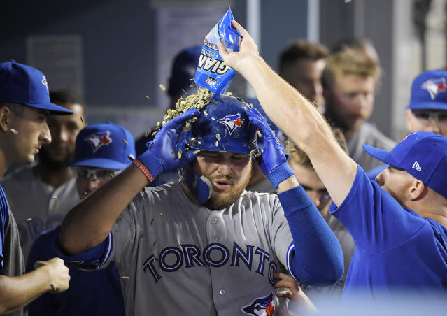A Toronto Blue Jay pours sunflower seeds over Rowdy Tellez, who had hit a solo home run during the ninth inning of the team's baseball game against the Los Angeles Dodgers on Wednesday, Aug. 21, 2019, in Los Angeles. (AP Photo/Mark J. Terrill)