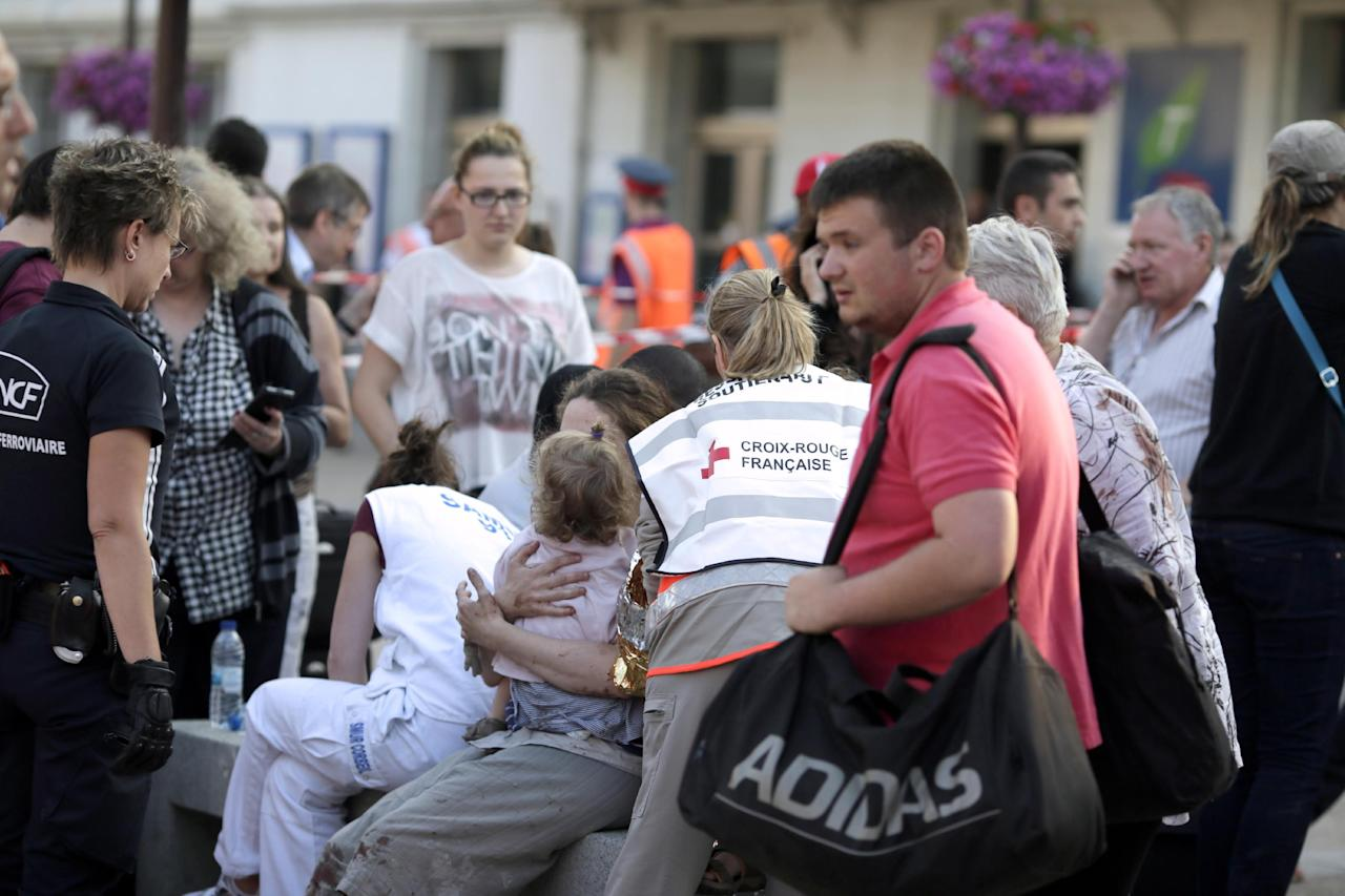 A woman holds a child amidst a rail worker and a Red Cross worker on the site of a train accident at Bretigny-sur-Orge train station Friday, July 12, 2013 near Paris. A packed passenger train skidded off its rails after leaving Paris on Friday, leaving seven people believed dead and dozens injured as train cars slammed into each other and overturned, authorities said.(AP Photo/Kenzo Tribouillard, Pool)