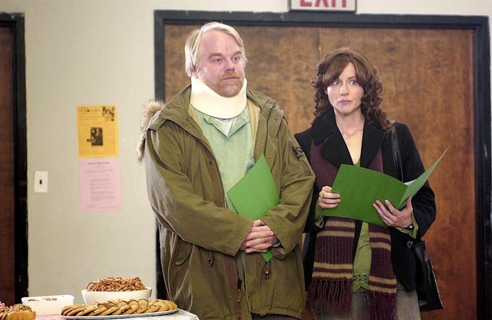 Philip Seymour Hoffman and Laura Linney holding green folders next to a table of food.