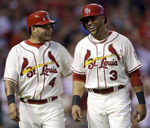 St. Louis Cardinals' Carlos Beltran, right, and Yadier Molina smile after scoring on a single by Ty Wigginton during the seventh inning of the second game of a baseball doubleheader against the San Francisco Giants, Saturday, June 1, 2013, in St. Louis. (AP Photo/Jeff Roberson)